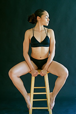 Mixed Race woman wearing underwear sitting on stool - p555m1491130 by Peathegee Inc