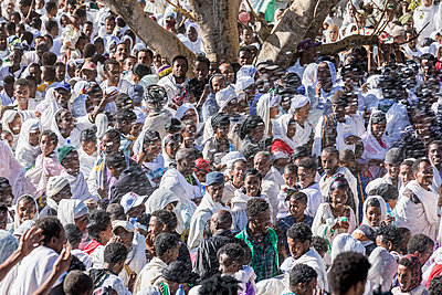 Ethiopia, Amhara Region, Lalibela. The crowd attending the annual Timkat festival of the Ethiopian Orthodox Church, which celebrates Epiphany, is sprayed with holy water at a baptismal pool. - p652m1487604 by Nigel Pavitt