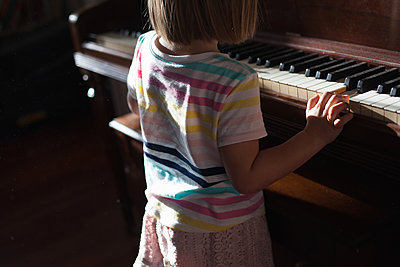 Rear mid section view of girl standing playing old piano at home - p924m1446954 by Kinzie Riehm