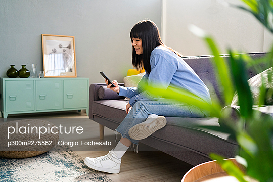 Smiling woman using smart phone while sitting on sofa in living room at home - p300m2275882 by Giorgio Fochesato
