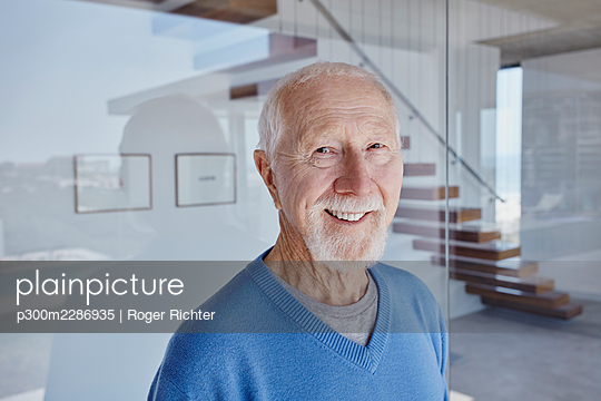 Smiling senior man standing in front of glass wall - p300m2286935 by Roger Richter