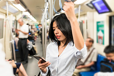 Businesswoman using cell phone in the subway - p300m1562198 by William Perugini
