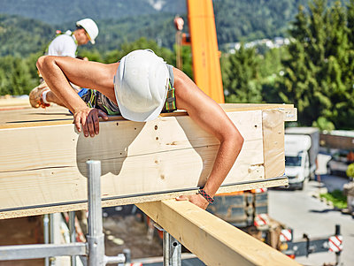 Austria, worker checking roof construction - p300m1567840 by Christian Vorhofer