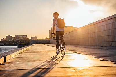 Young man with backpack riding bike on waterfront promenade at the riverside at sunset - p300m2059655 by Vasily Pindyurin