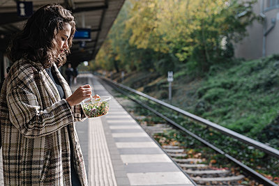Woman having lunch on an underground station platform, Berlin, Germany - p300m2143390 by Hernandez and Sorokina