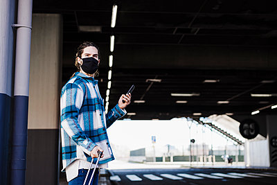 Man wearing face mask using mobile phone while standing on underpass road - p300m2242373 by Eva Blanco