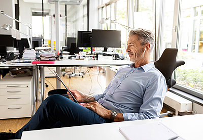 Businessman using digital tablet while relaxing on chair at open plan office - p300m2257103 by Peter Scholl