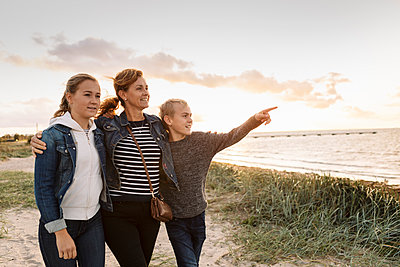 Smiling son pointing while mother and daughter standing against cloudy sky at beach - p426m2205430 by Kentaroo Tryman