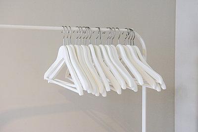 Kleiderbügel hängen auf Kleiderstange - p567m1090787 von GINA VAN HOOF