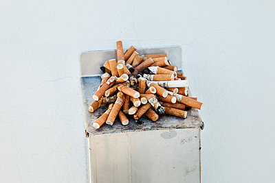 An outdoor ashtray overflowing with cigarettes and cigarette butts  - p8476248 by Sara Arnald