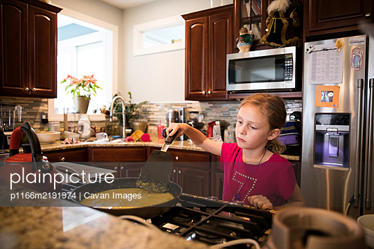 Candid Image of Unsmiling Young Girl Cooking Eggs In Messy Kitchen - p1166m2191974 by Cavan Images