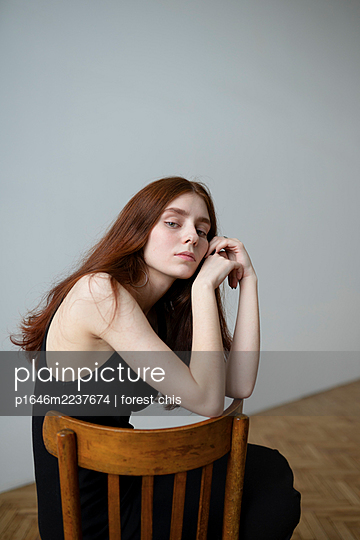 Young woman with brown hair sits on chair - p1646m2237674 by Slava Chistyakov