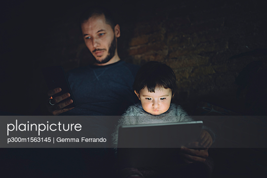 Father and daughter using phablet  and digital tablet at home in the dark - p300m1563145 by Gemma Ferrando