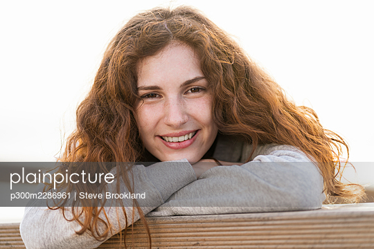 Portrait of a happy and relaxed young woman with red hair at the beach - p300m2286961 von Steve Brookland