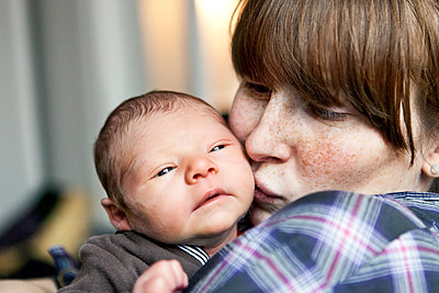 Freckled mother kissing her newborn baby son on the cheek - p300m1525860 by Mareen Fischinger