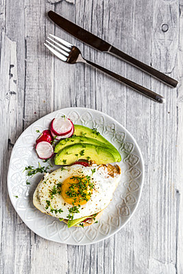 Toast with with fried egg, avocado, red radish, tomato and cress - p300m1581756 von Sandra Roesch