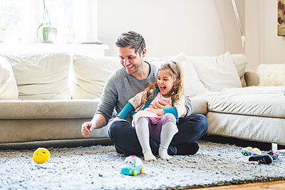 Cheerful father and daughter looking at toy while playing at home - p426m2127429 by Maskot