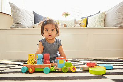 Portrait of baby girl sitting on rug playing with toy train - p429m1448261 by Emma Kim