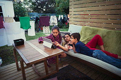 Mother and children using digital tablet in backyard - p555m1312086 by Donald Iain Smith
