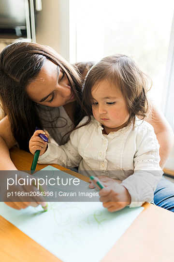 Nanny helping a toddler with a drawing with colored pencils - p1166m2084998 by Cavan Images