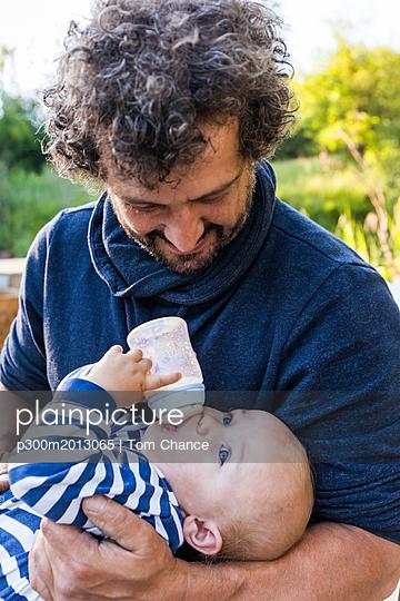 Father watching his baby boy drinking - p300m2013065 von Tom Chance