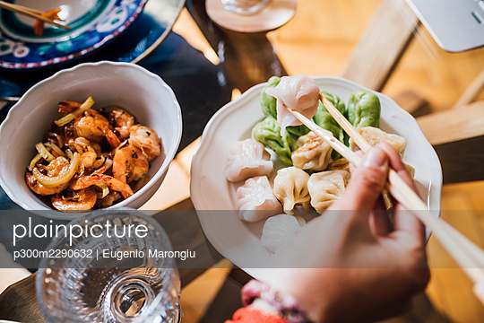Woman holding chopsticks while eating lunch at home - p300m2290632 by Eugenio Marongiu