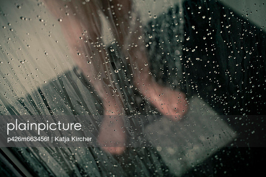 Transparent wet glass in domestic bathroom with low section of a boy bathing in background - p426m663456f by Katja Kircher