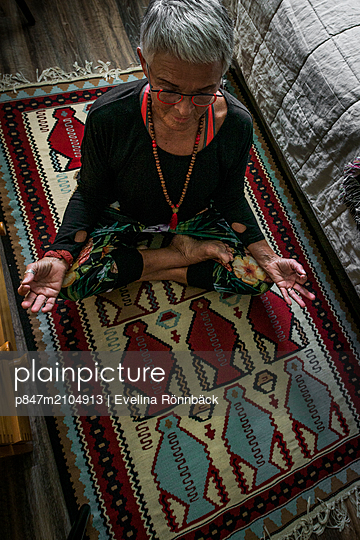 Relaxed Old Woman Practising Yoga At Home   - p847m2104913 by Evelina Rönnbäck