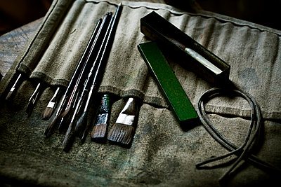 A row of paint brushes and hand tools. - p1100m1158327 by Mint Images