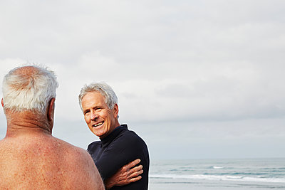 Two senior men standing on a beach chatting, one wearing a wetsuit.  - p1100m1177583 by Mint Images
