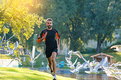 Man running at the riverside surrounded by seagulls - p300m1175747 by Daniel Ingold