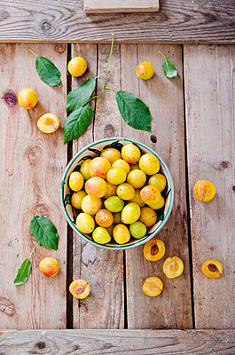 Mirabelles in a bowl on a wooden tray - p300m838451f by Canan Czemmel