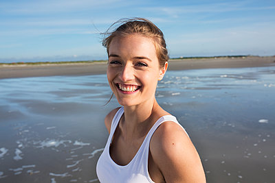 Young woman on St. Peter-Ording beach - p341m1480691 by Mikesch