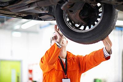 College mechanic student inspecting car wheel in repair garage - p429m1226904 by Peter Muller