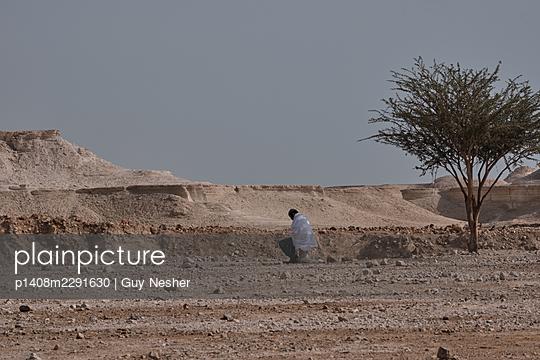 Praying man in desert - p1408m2291630 by Guy Nesher