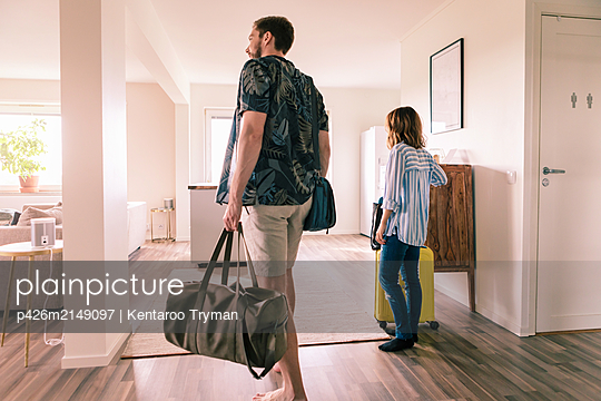 Couple walking with luggage in apartment during staycation - p426m2149097 by Kentaroo Tryman