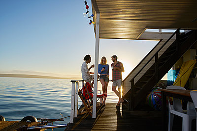 Young adult friends hanging out on summer houseboat on ocean - p1023m1217946 by Francis Pictures