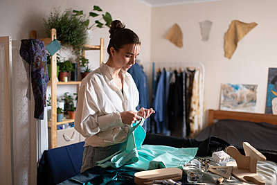Young woman sewing in home atelier - p1166m2218563 by Cavan Images