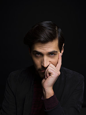 Portrait serious handsome brunette man with head in hand against black background - p1192m1403586 by Hero Images