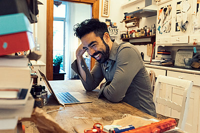 Lachender Hipster mit Macbook im Home Office - p1491m1582705 von Jessica Prautzsch
