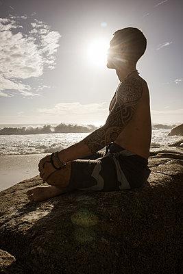 Mann meditiert auf dem Strand in der Abendsonne - p1640m2261010 von Holly & John