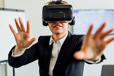 Businesswoman gesturing while wearing virtual reality simulator in office - p300m2276147 by Eugenio Marongiu