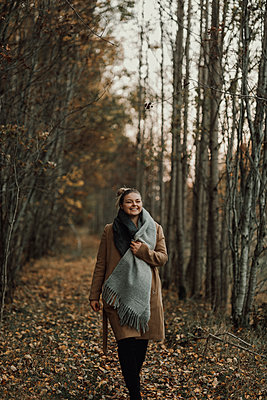 Woman walking through autumn forest - p312m2191146 by Jennifer Nilsson