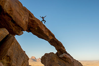 Man jumping on top of rock arch, Spitzkoppe, Erongo region, Namibia - p343m1486349 by jeanlouis Wertz