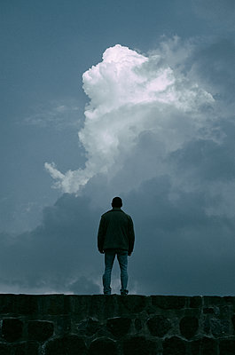 Rear view of a man standing against a cloudy sky  - p794m1538285 by Mohamad Itani