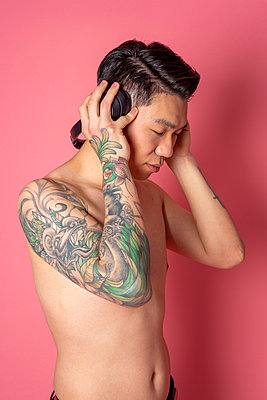 Asian man with tattoos and headphones - p817m2159120 by Daniel K Schweitzer