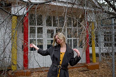 Woman in front of an abandoned building - p1646m2224612 by Slava Chistyakov