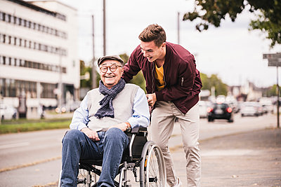 Young man pushing happy senior man in wheelchair - p300m2144890 by Uwe Umstätter
