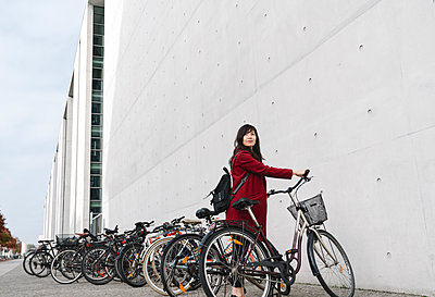 Businesswoman taking bicycle in the background of modern building - p300m2155200 by Hernandez and Sorokina