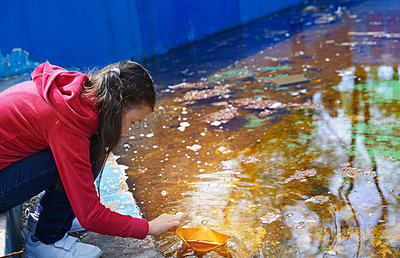 Innocent girl playing with paper boat at pond - p300m2281487 by Arman Zhenikeyev